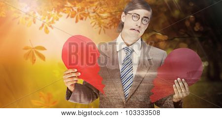 Geeky businessman crying and holding broken heart card against autumn scene
