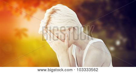Sad blonde woman crying with head on hands against autumn scene
