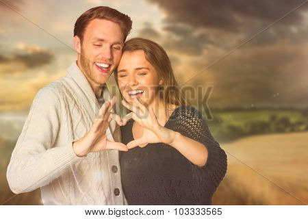 Happy couple forming heart with hands against country scene