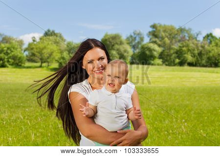 Toddler and his mummy carrying him in meadow