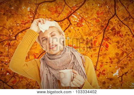 Close up of woman feeling her forehead against autumn scene