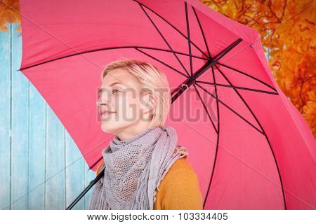 Happy woman keeping dry against autumn leaves pattern