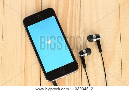 iPhone with Twitter logotype on its screen and headphones