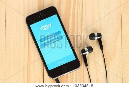 iPhone with Skype logotype on its screen and headphones on wooden background