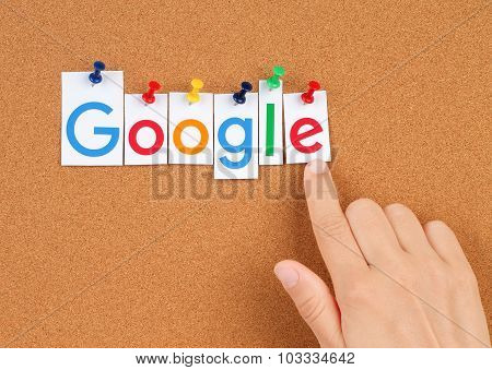 New Google logotype printed on paper, cut and pinned on cork bulletin board with hand