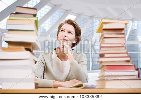Thoughtful teacher at library against modern room overlooking city