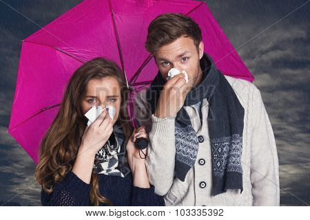 Couple blowing nose while holding umbrella against cloudy sky