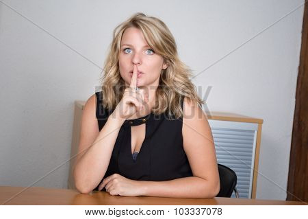 Blond Young Woman With Finger On Her Mouth