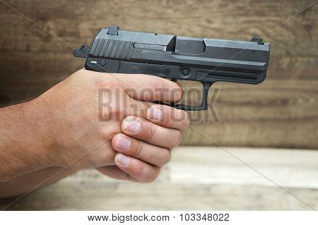 masculine Hand Holding Pistol Gun