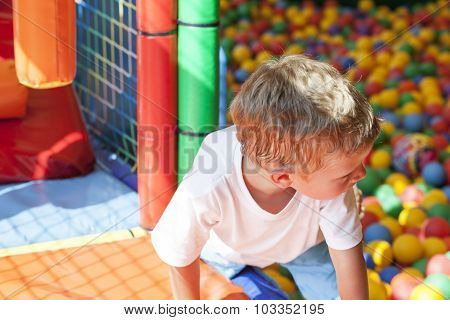 Little Boy Playing In Colorful Balls Playground
