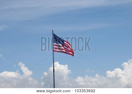 Flag of United States of America waving in the mast with blue sky background