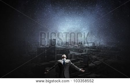 Businessman with hands spread apart on city landscape background