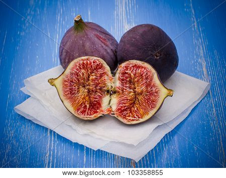 Three Ripe Figs On Baking Paper, Blue Wooden