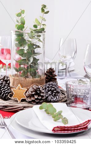 Christmas table place setting in red and white and rustic pine cone centerpiece