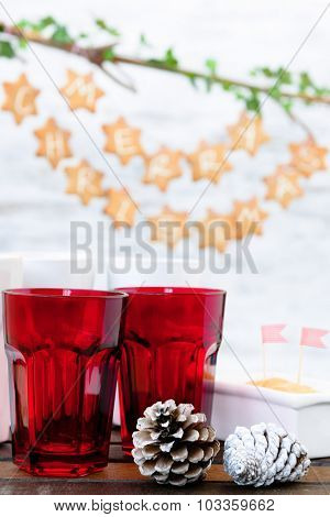 Christmas decoration table with red cups, cake with striped flags, pine cones and gingerbread stars hanging in the background
