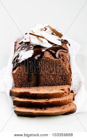 Loaf of chocolate cake with rich chocolate ganache flowing and coconut pieces
