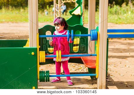 little girl playing at the playground in autumn