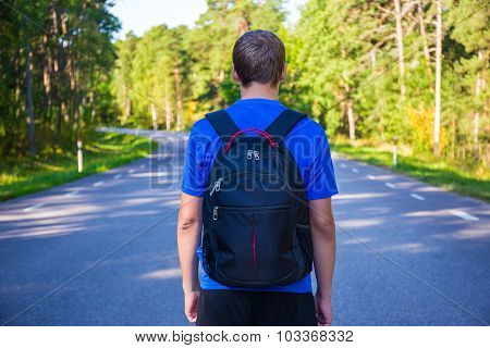 Hiking Concept - Back View Of Man Walking On Forest Road
