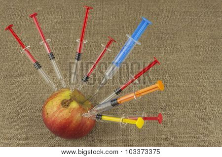 Genetic modification concept. Fruit and syginge.