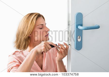 Young Woman Fixing Door