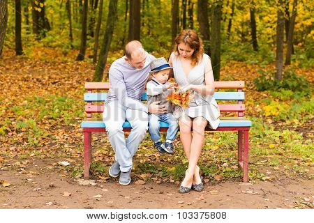 Young family for a walk in the autumn park with baby