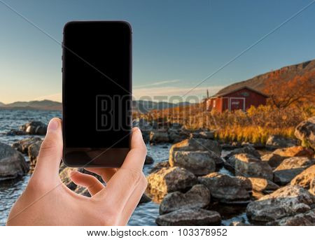 Hand holding mobile with black screen on scandinavian background