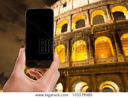 Hand holding mobile with black screen with Colosseum background