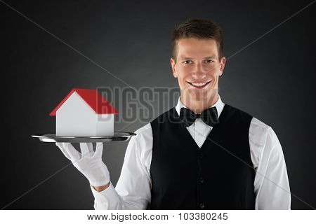 Butler Holding Tray With House Model