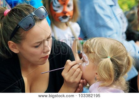makeup artist draws on the child's face mask tiger