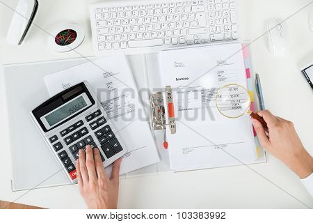 Businessperson Examining Invoice With Magnifying Glass