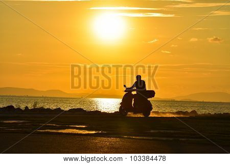 Man biker over sunset, male riding motorcycle.