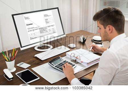 Accountant Calculating Tax At Desk