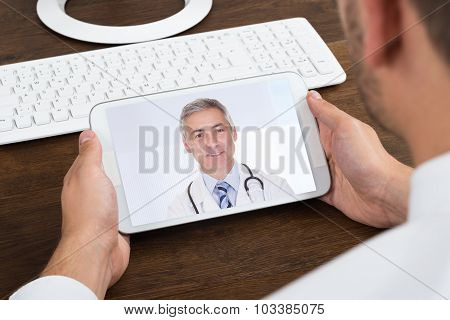 Businessperson Videochatting With Senior Doctor