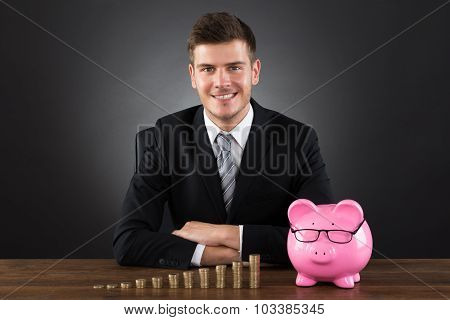 Businessman With Coins And Piggybank