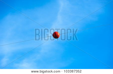 Single Orange Warning Sphere On Cable Against Sky