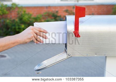 Person Removing Letters From Mailbox