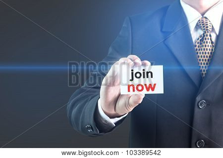 A Businessman holding a white sign with the message join now.