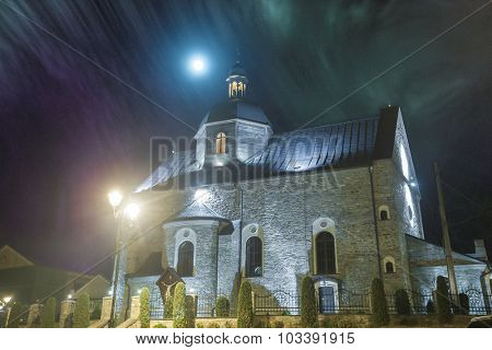 The beautiful medieval church in the night light and fog