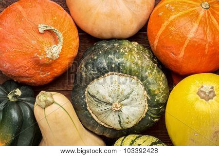 a variety of winter squash fruits on a rustic wooden table, top view