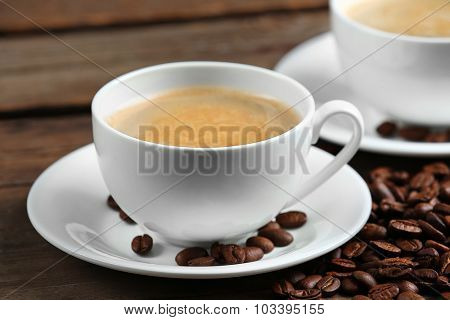 Cups of coffee and beans on wooden table close up