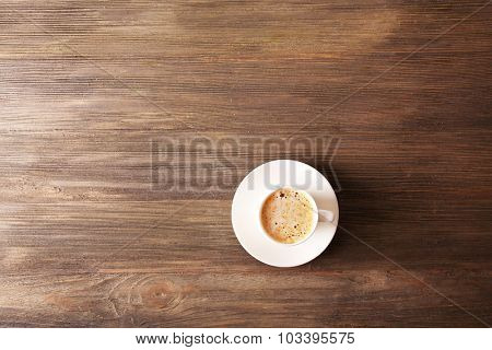 Cup of coffee with foam on wooden table, top view