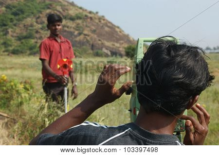 Two surveyors at work in a field in South India