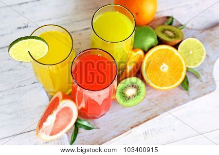 Glasses of different juice with fruits and mint on table close up