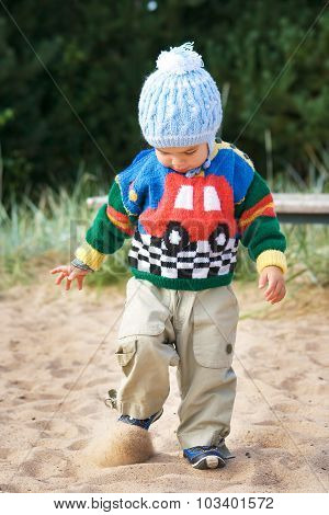 Walking boy in knitted sweater and hat