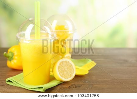 Yellow vegetable and fruit salad and healthy fresh drink in plastic cups on wooden  table, on bright background. Colorful diet concept