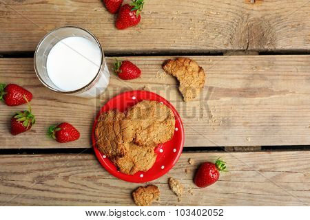 Homemade cookies with strawberries and glass of milk on table close up