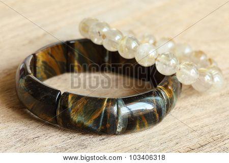 Lucky Stone Bracelets On Wood Background