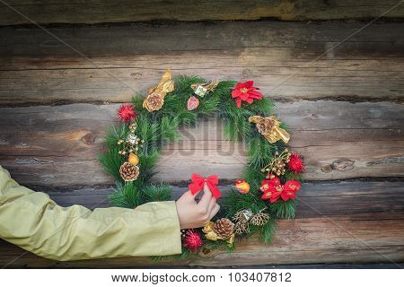 Woman Arm Holding Red Bow And Decorating Outdoor Log Cabin Wall With Christmas Wreath