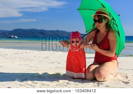 mother and daughter with umbrella on beach vacation