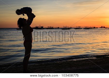 mother and baby at sunset beach